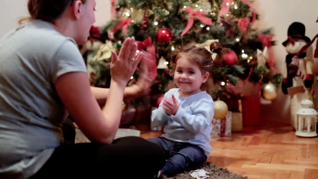 mother and her baby playing clapping games and hugging under the christmas tree - tree hugging stock videos & royalty-free footage