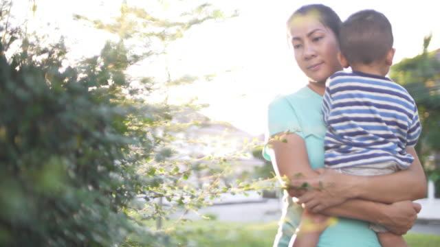 slo mo 母親と夕日と公園で遊んで赤ちゃん - 目が回る点の映像素材/bロール