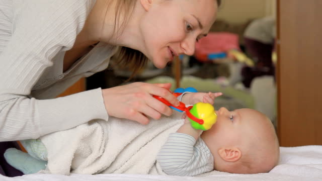 Mother and her baby playing with rattles.