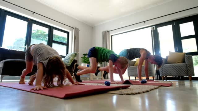 mother and her children doing an online fitness class at home - quarantena video stock e b–roll