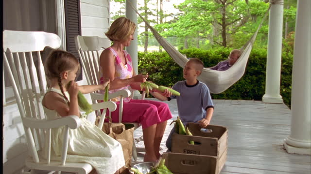 A mother and her children shuck corn while Dad relaxes in the porch hammock.