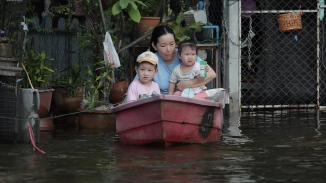 a mother and her children sit in a boat tethered to their house in bang prok pathum thani thailand heavy monsoon rains have been drenching southeast... - bronek kaminski stock videos & royalty-free footage