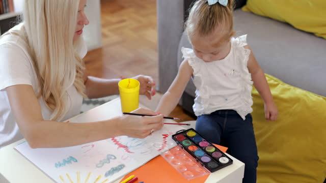 madre e sua figlia stanno dipingendo e divertendosi a casa - capelli biondi video stock e b–roll