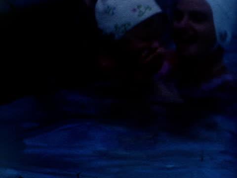 vídeos de stock, filmes e b-roll de a mother and her daughter enjoy a swimming pool. - touca de natação