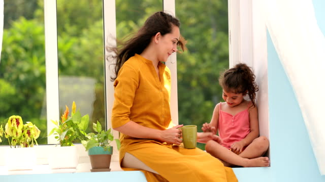 ms mother and her daughter having fun together while sitting on window sill at home / chhatarpur, delhi, india - image stock videos & royalty-free footage