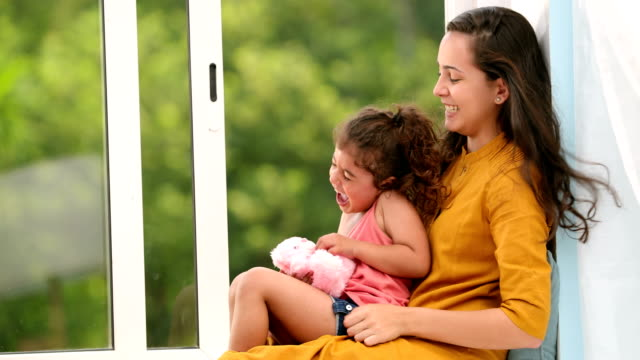 ms mother and her daughter having fun together while sitting on window sill at home / chhatarpur, delhi, india - indian ethnicity stock videos & royalty-free footage