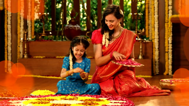 MS Mother and her daughter making flower rangoli during pongal festival / New Delhi, India
