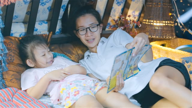 mother and her daughter reading bedtime stories together - narrare storie video stock e b–roll
