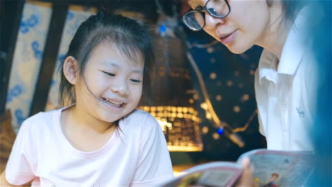 mother and her daughter reading bedtime stories together - fairy tale stock videos & royalty-free footage