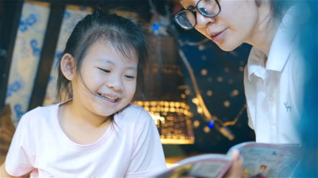 mother and her daughter reading bedtime stories together - ora di andare a letto video stock e b–roll