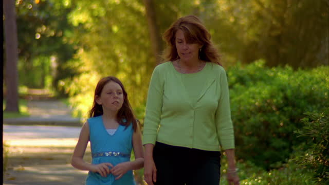 a mother and her daughter walk and talk together in their suburban neighborhood. - 2005 stock videos and b-roll footage