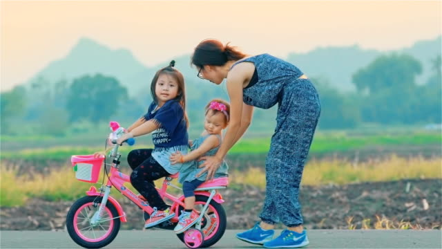 mother and her daughter with bicycle in countryside together - stabilisers stock videos & royalty-free footage