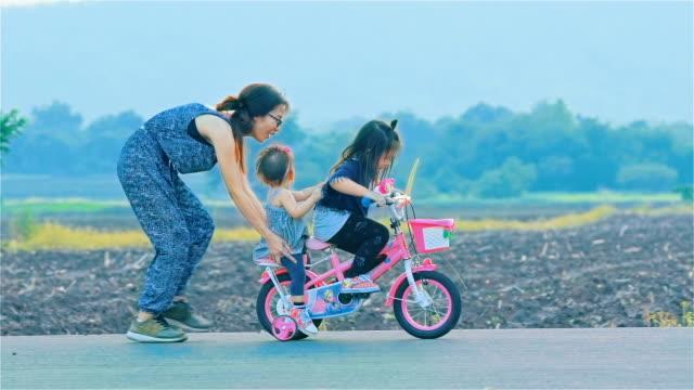 vídeos y material grabado en eventos de stock de madre y su hija con bicicleta en campo junto - enseñar