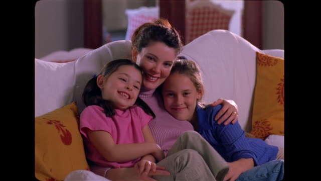 vidéos et rushes de a mother and her daughters share tickles on the couch. - chatouiller