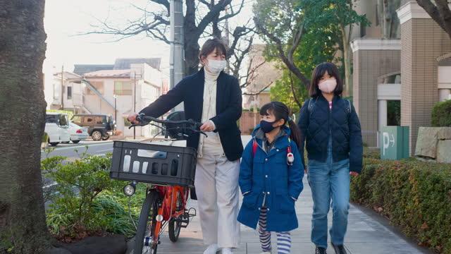 通りを歩いている母親と娘たち。母親は娘たちが学校に行く仕事に行く - 新学期点の映像素材/bロール