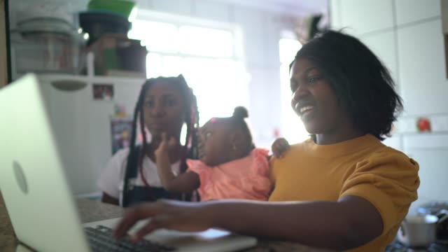 mother and her family having fun while he is using laptop at home - parent stock videos & royalty-free footage