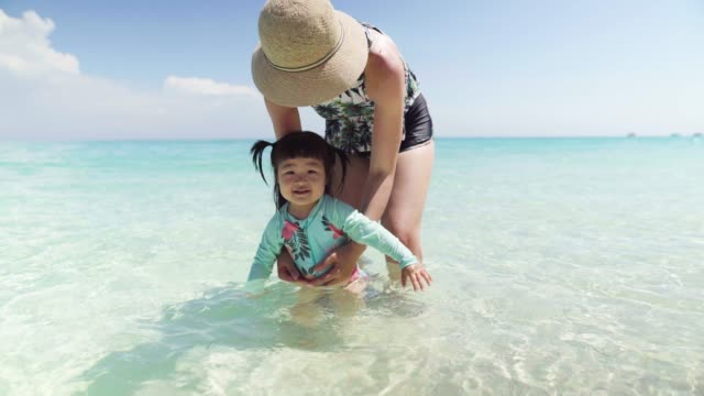 mother and her happy little girl having fun in the sea - malaysia stock videos & royalty-free footage