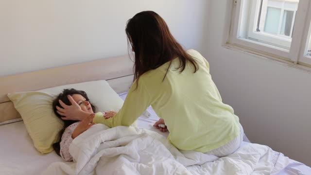 stockvideo's en b-roll-footage met moeder en haar zieke dochter in slaapkamer - dubbel bed