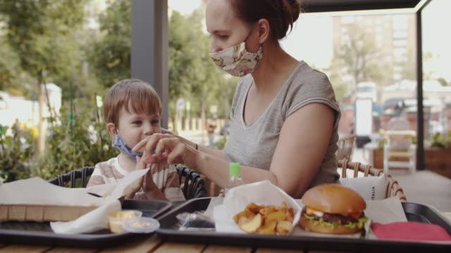 vídeos y material grabado en eventos de stock de madre y su pequeño niño con máscara protectora reutilizable en un café. nuevo concepto normal. - cámara en mano
