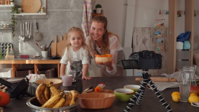 mother and her little daughter showing off their dessert to the camera - tutorial stock videos & royalty-free footage
