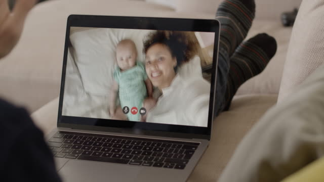 mother and her newborn baby in bed making video call to family member on sofa using laptop - video call stock videos & royalty-free footage