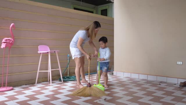 stockvideo's en b-roll-footage met moeder en haar zoon zijn het schoonmaken van het huis - spelletjesavond