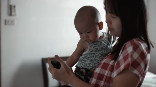 mother and her son looking at her smartphone and using application - thai ethnicity stock videos & royalty-free footage