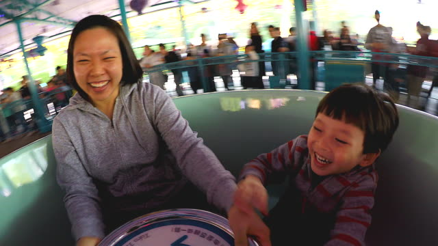 Mother and her son sitting on a rotating chair cup enjoying the speed of stimulation and clutching the steering wheel in the amusement park on the vacation holidays.