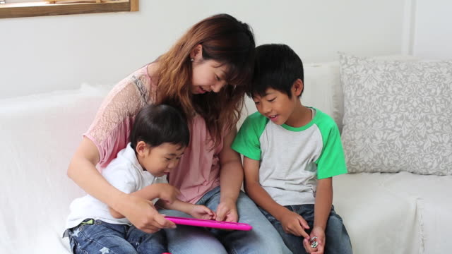 A mother and her sons using a tablet together in the livingroom