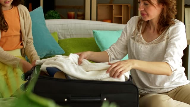 mother and her teenage daughter packing a suitcase together - bagaglio video stock e b–roll