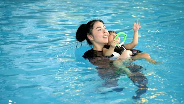 4k ms mutter und ihr kind in einem pool schwimmen - kopf nach hinten stock-videos und b-roll-filmmaterial