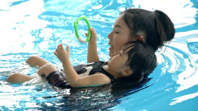 slomo-mutter und ihr kind in einem pool schwimmen - kopf nach hinten stock-videos und b-roll-filmmaterial