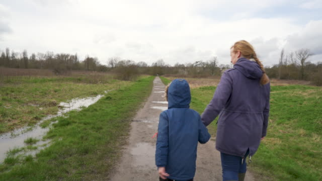 a mother and her two young sons walking through a muddy park - mud stock videos & royalty-free footage
