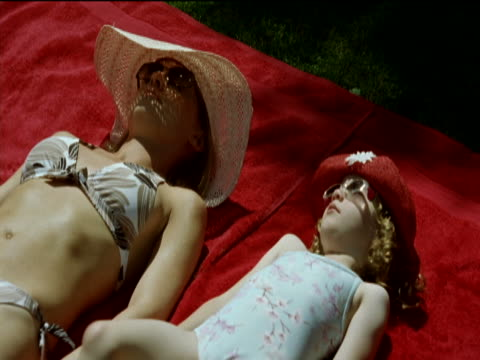mother and her young daughter sunbathing side by side wearing swimsuits, sunhats and sunglasses look at each other and smile - side by side stock videos & royalty-free footage