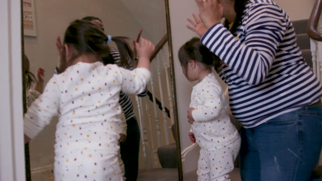 a mother and her young daughters with downs syndrome looking in a mirror together - candid stock videos & royalty-free footage