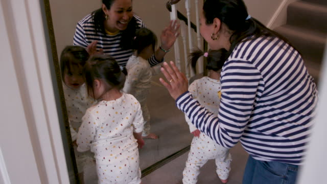 a mother and her young daughters with downs syndrome looking in a mirror together - sign language stock videos & royalty-free footage