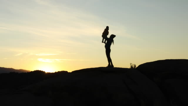 vídeos de stock e filmes b-roll de a mother and her young son hiking and playing on rock at sunrise. - plano picado