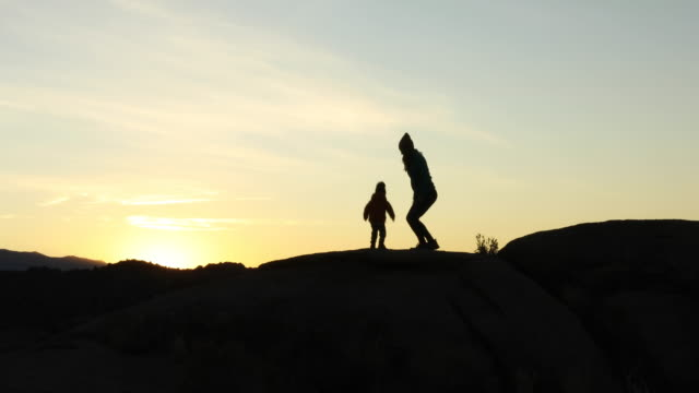 a mother and her young son hiking and playing on rock at sunrise. - single mother stock videos & royalty-free footage