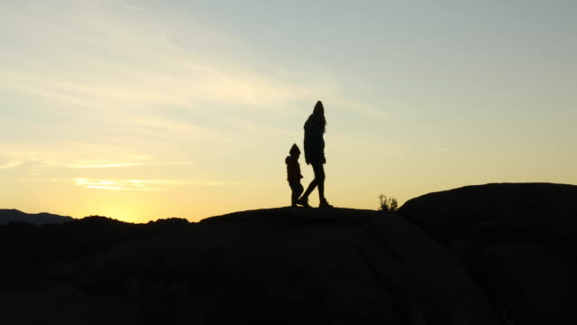 a mother and her young son hiking and playing on rock at sunrise. - childhood stock videos & royalty-free footage