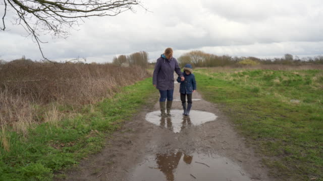 a mother and her young son rinsing the mud off of their wellington boots in a puddle - mud stock videos & royalty-free footage