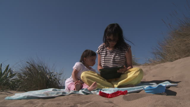mother and his girl playing with digital tablet in dunes - sun visor stock videos and b-roll footage