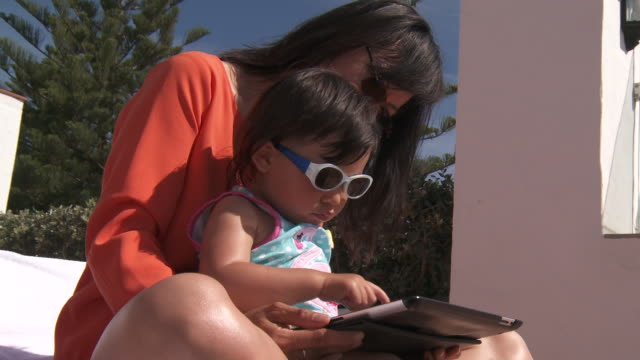 mother and his girl playing with digital tablet. - abbigliamento da neonato video stock e b–roll