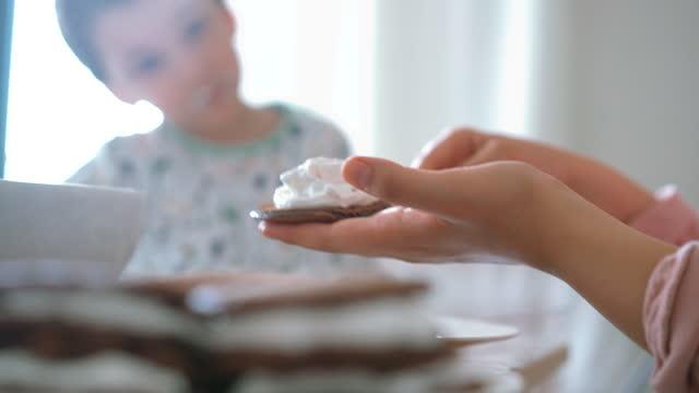 mutter und sein kleiner süßer sohn machen pfannkuchen zusammen - sahne stock-videos und b-roll-filmmaterial