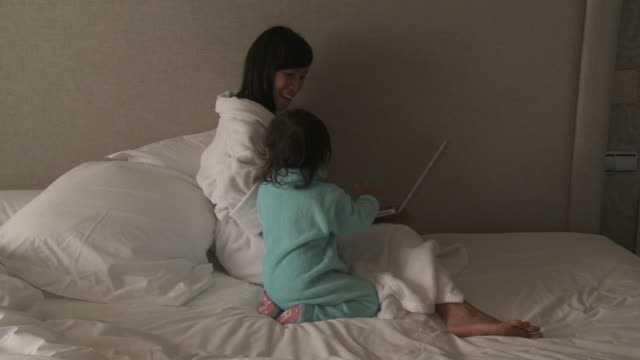 Mother and his little girl playing on computer