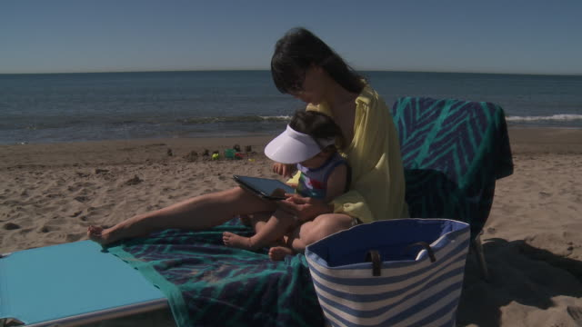 mother and his little girl playing with digital tablet at the beach. - sun visor stock videos & royalty-free footage