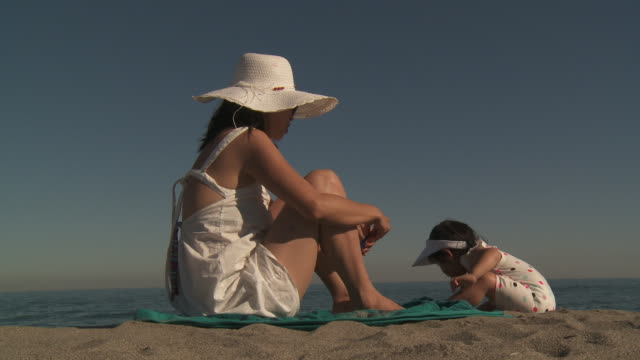 mother and his little metis girl playing on the beach. - サンドレス点の映像素材/bロール
