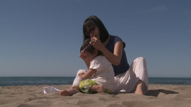mother and his little metis girl playing on the beach. - sun visor stock videos & royalty-free footage