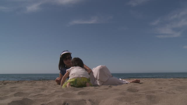 Mother and his little Metis girl playing on the beach.