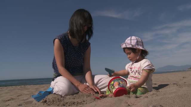 vídeos de stock e filmes b-roll de mother and his little metis girl playing on the beach. - vida de bebé