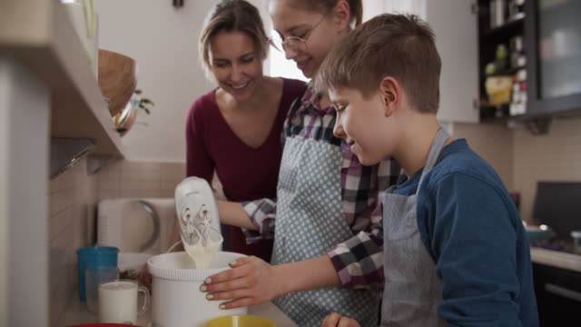 mother and kids making yeast cake - three people stock videos & royalty-free footage